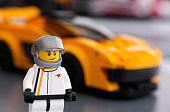 Tambov, Russian Federation - March 09, 2015: Lego McLaren P1 driver minifigure by LEGO Speed Champions and his car on background. Focus on the driver uniform. Studio shot.