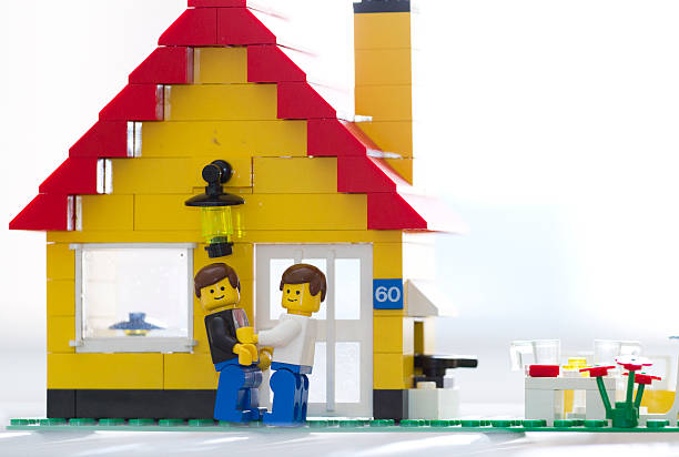lego mini figure gay man embrace front of their house - lego house stock photos and pictures
