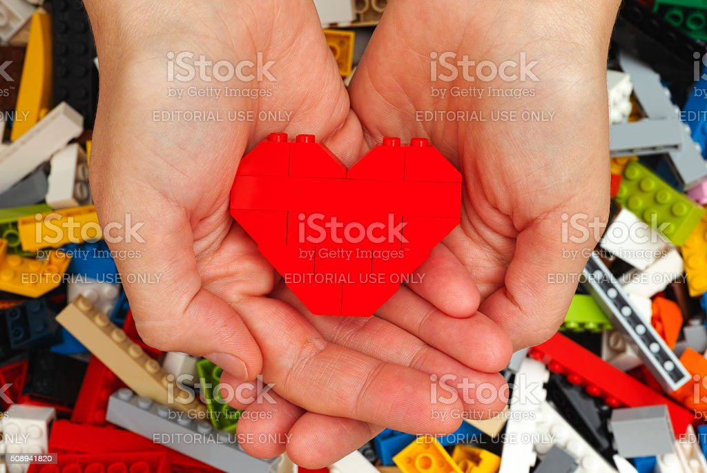 Lego red heart in woman hands stock photo