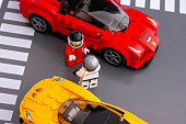 Tambov, Russian Federation - March 09, 2015: Lego drivers standing in front of each other by LEGO Speed Champions and his car. There are Lego LaFerrari and Lego McLaren P1 cars models. Studio shot.