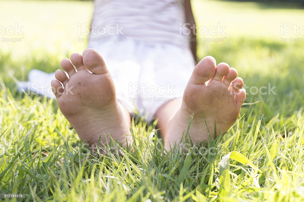Ноги и Ступни девушки на траве стоковое фото