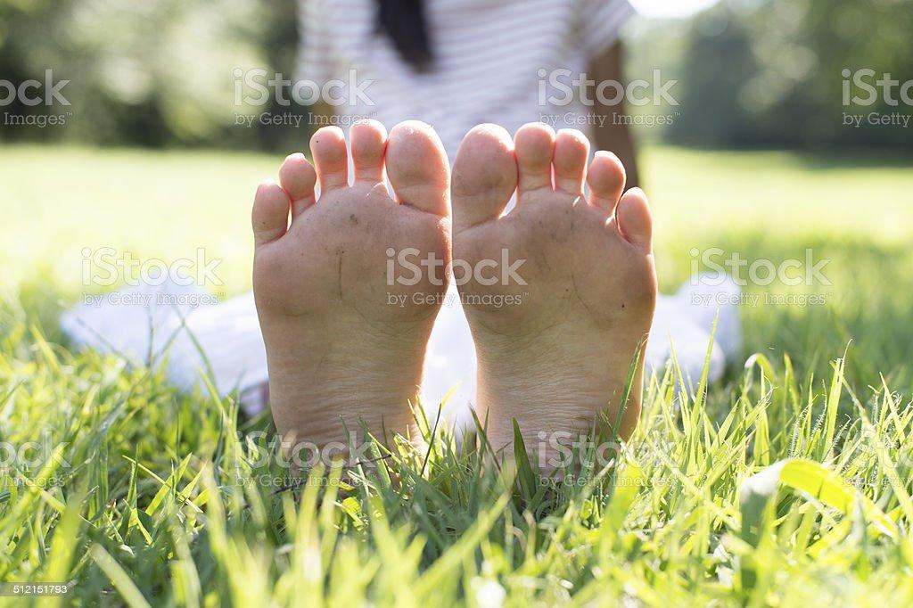 Las piernas y pies de chica en hierba - foto de stock