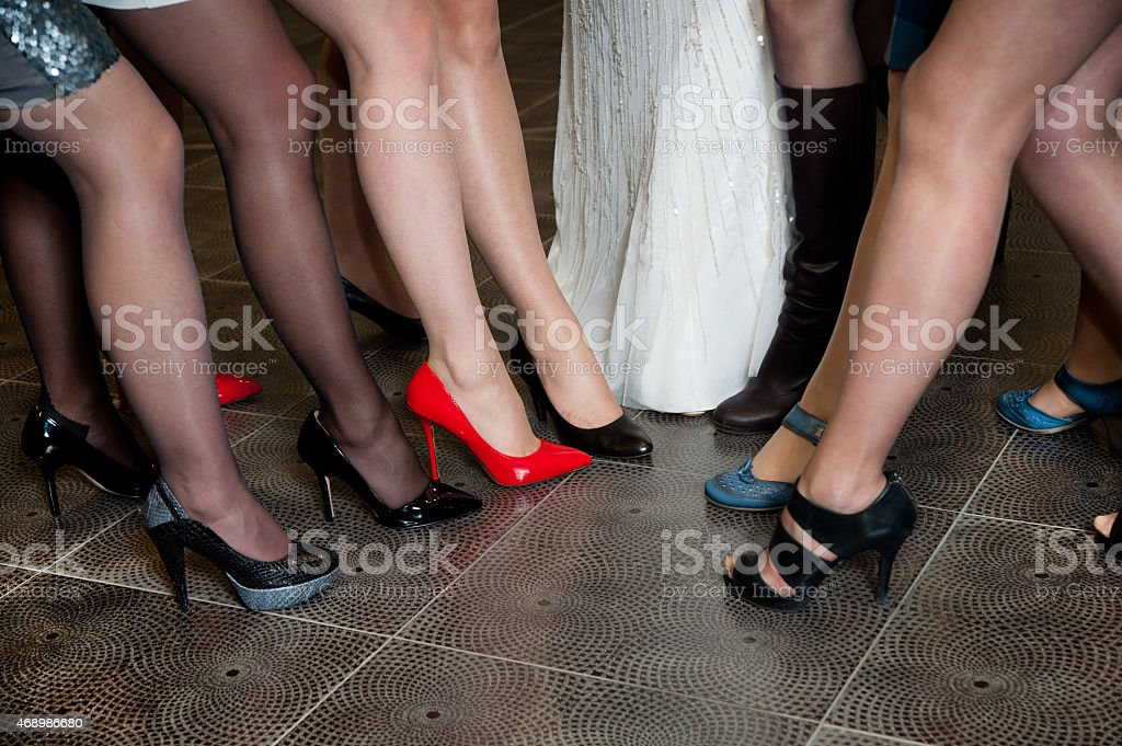 Legs and feet of bridesmaids wearing high-heeled shoes stock photo