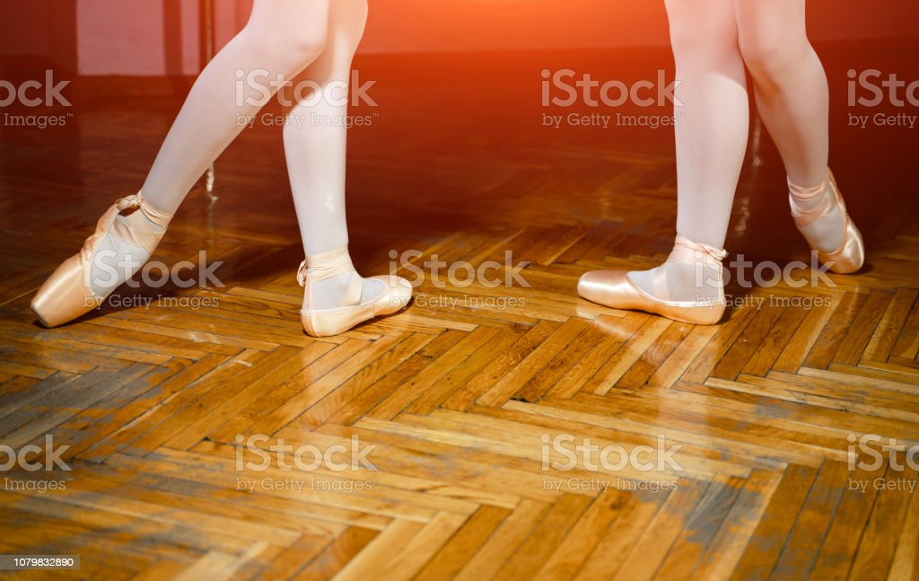 Legs and feet of two ballet dancers wearing pointe shoes and white...