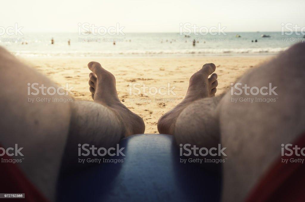 Beine und Füße des jungen männlichen Touristen liegen auf Strandkorb vor klares Wasser und blauer Himmel mit Sonne – Foto