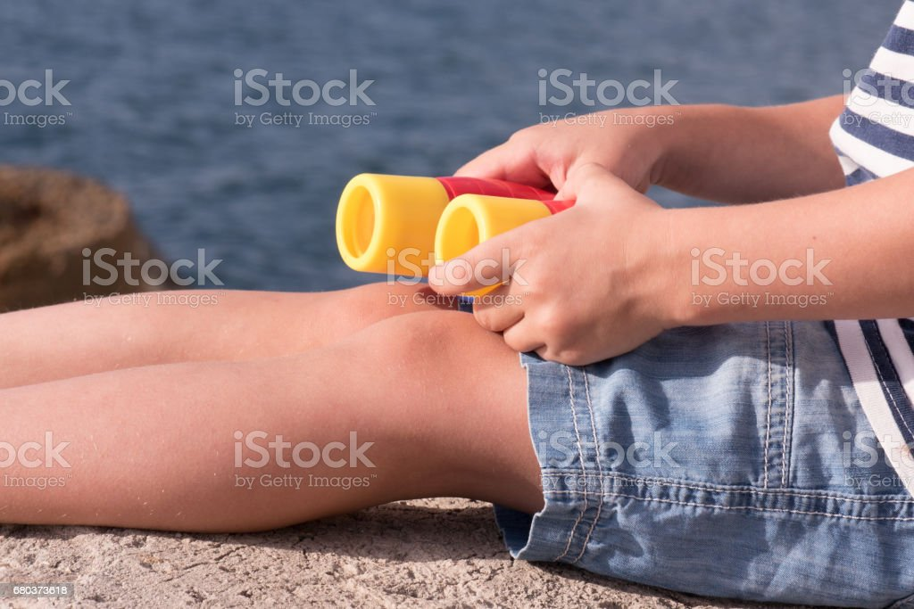 legs and hands a little boy in shorts holding binoculars on sea background stock photo