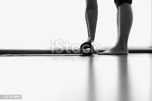 istock Legs and hands of woman folding yoga mat in bright studio room 1027629892