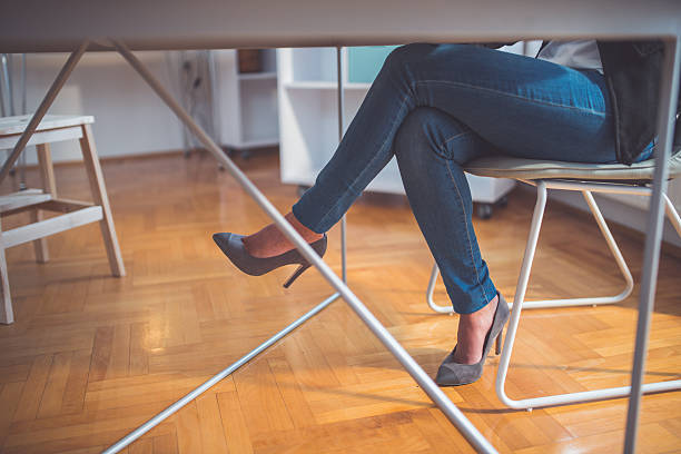 Legs and high heels Low angle view on legs while sitting at the office table cross legged stock pictures, royalty-free photos & images