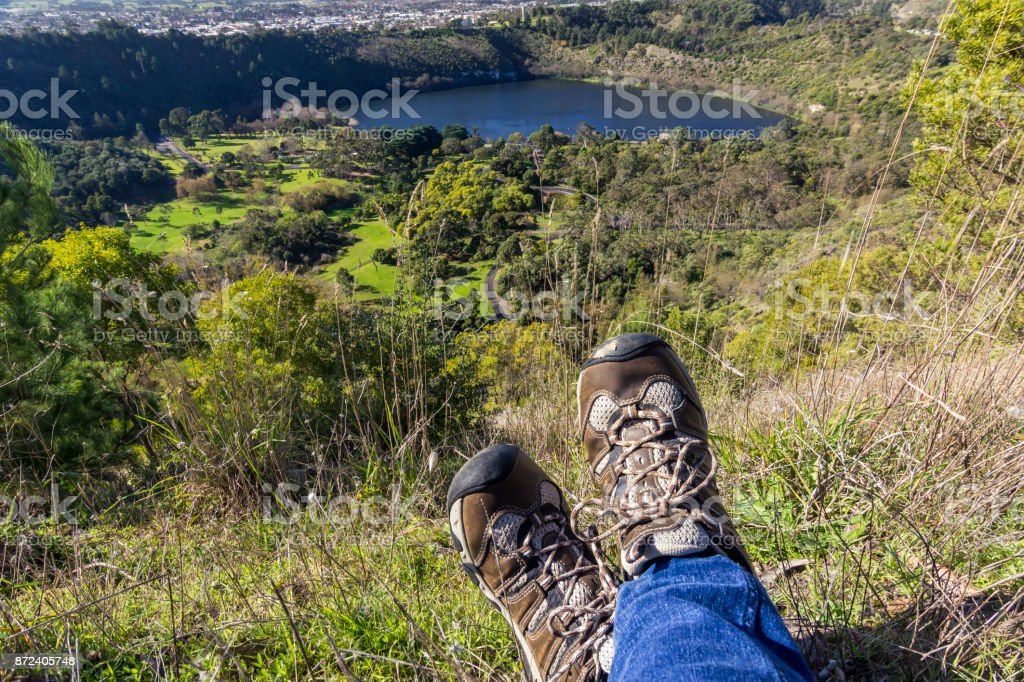 Legs and hiking shoes of a traveler sitting on a mountain top looking over a blue lake. stock photo