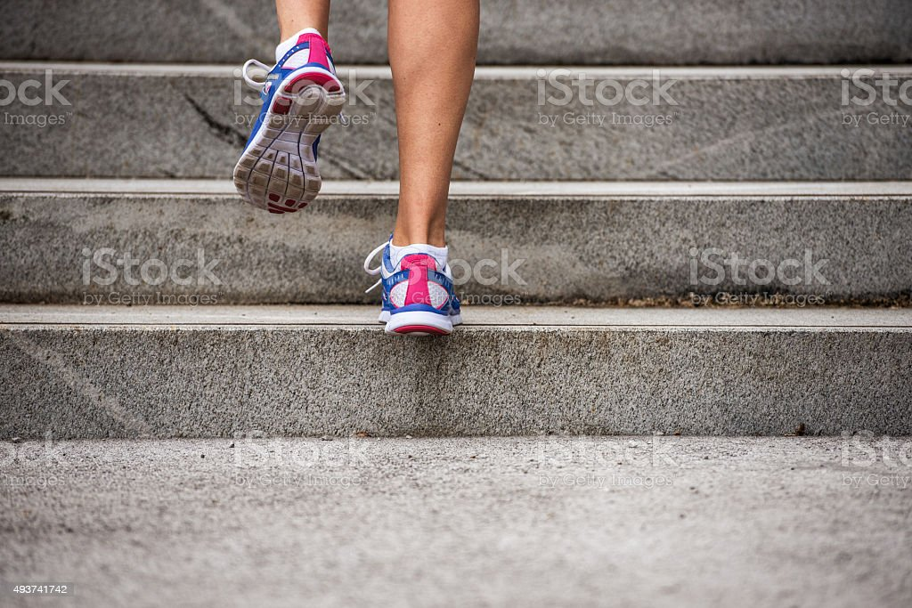 Legs and Shoes of a Jogger Running up a Staircase stock photo