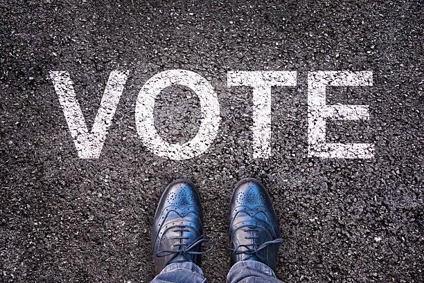 """legs and shoes on asphalt with the word """"vote"""" - wettervorhersage deutschland stock-fotos und bilder"""