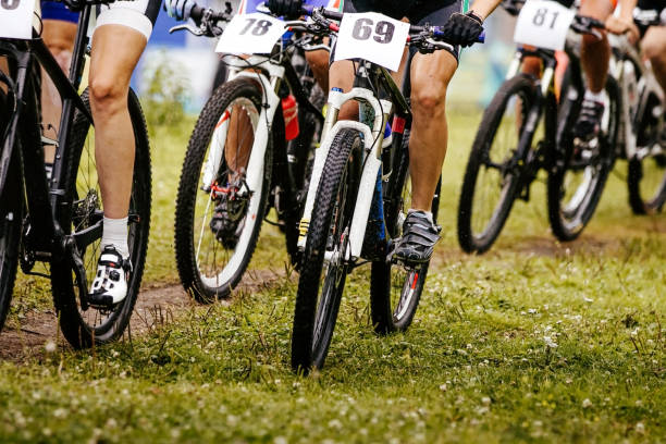 legs and wheels of bicycle riders cyclists stock photo