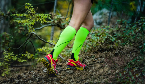 legs female runner in bright green compression socks stock photo