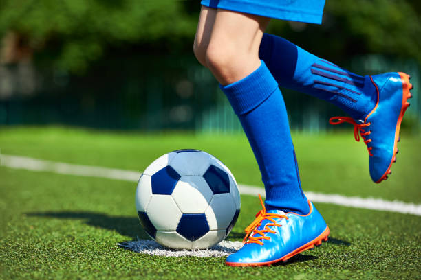Legs football player boy in boots with ball on grass stock photo