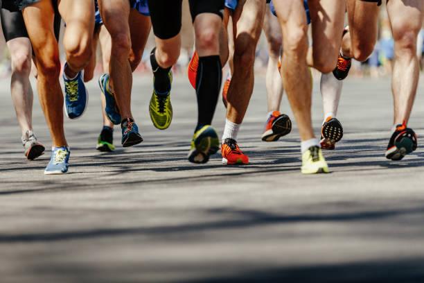 las piernas del grupo corredores hombres corriendo en carretera asfaltada - maratón fotografías e imágenes de stock