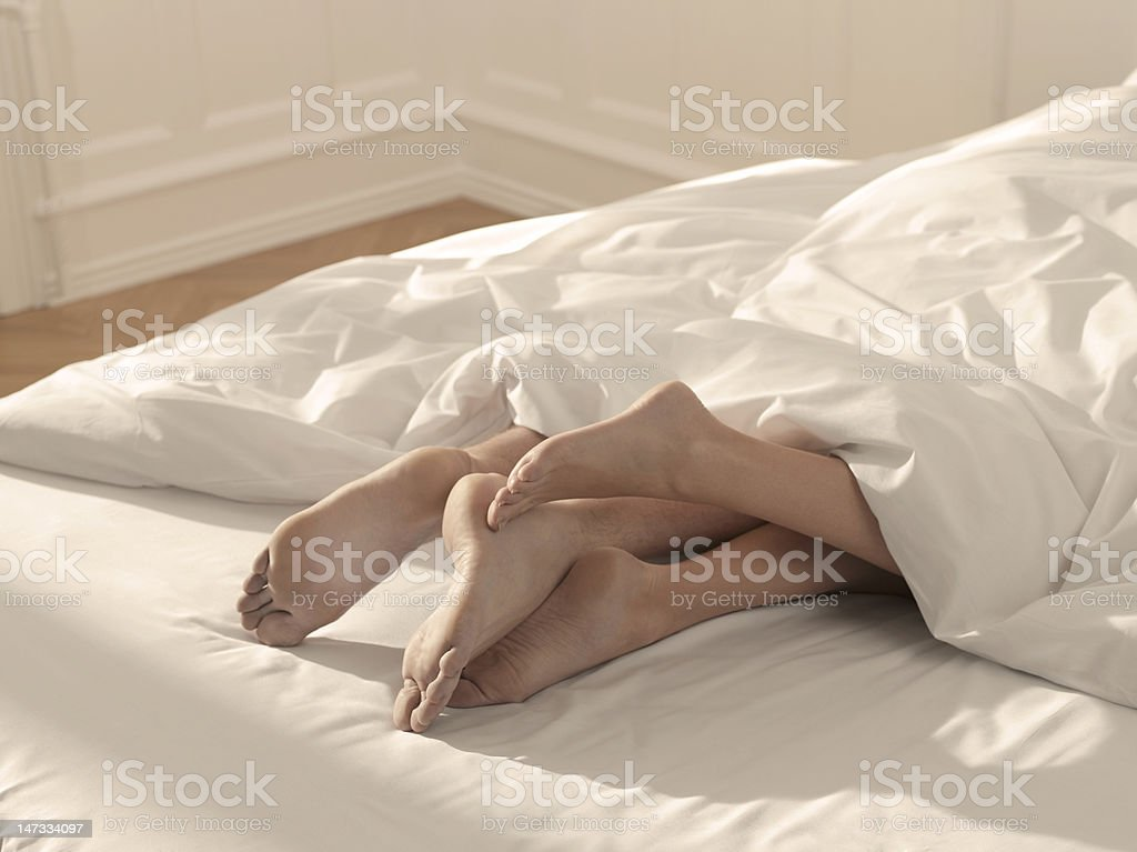 Legs in bed stock photo