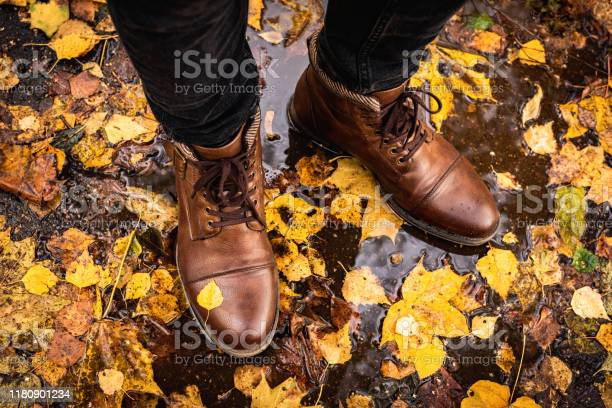 Photo of Legs in brown leather boots on wet asphalt