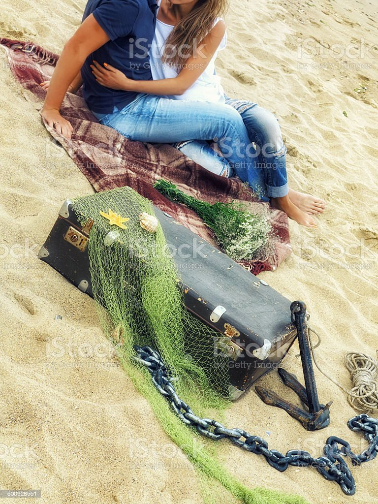 legs in jeans, men  women   plaid blanket on beach stock photo