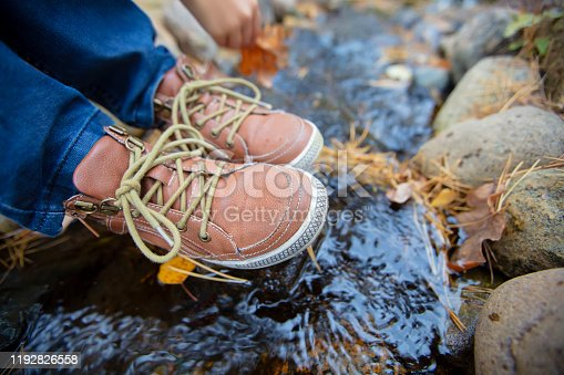665586146 istock photo Legs in leather shoes on a background of nature. Children's shoes at the waterfall. Travel and tourism concepts 1192826558