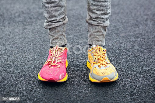 Which one should I choose? Legs in multi-colored running shoes.