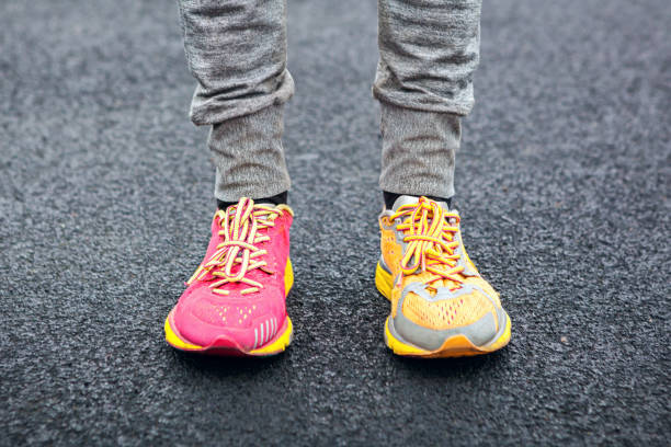 legs in multi-colored running shoes. - contrasti foto e immagini stock