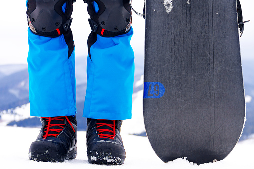 Legs in snowboarder boots with snowboard