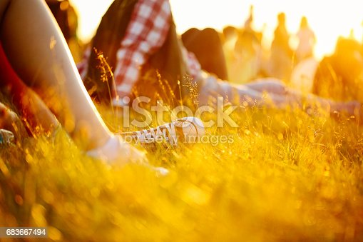 istock legs in sport shoes or sneakers in grass. summer lifestyle. Colorful warm yellow toning. People on holiday laying on ground. recreation in park nature. Music Festival on outdoor. Object photo 683667494