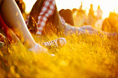 legs in sport shoes or sneakers in grass. summer lifestyle. Colorful warm yellow toning. People on holiday laying on ground. recreation in park nature. Music Festival on outdoor. Object photo