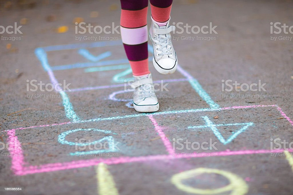 Legs in striped socks and white shoes playing hopscotch stock photo