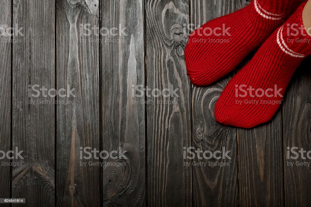 Legs knitted red wool socks on wooden dark background. stock photo