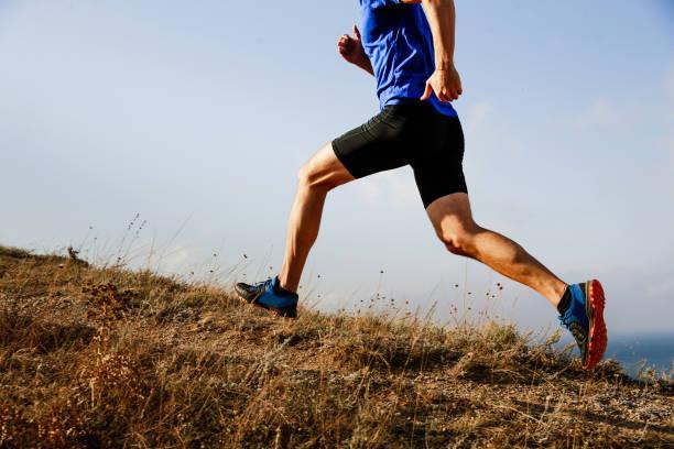 corredor de atleta masculino piernas corriendo cuesta arriba en el fondo del camino del cielo - foto de stock