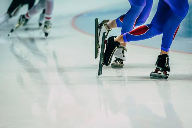 patinadores masculinos de las piernas durante el calentamiento antes de las competiciones de patinaje de velocidad - foto de stock