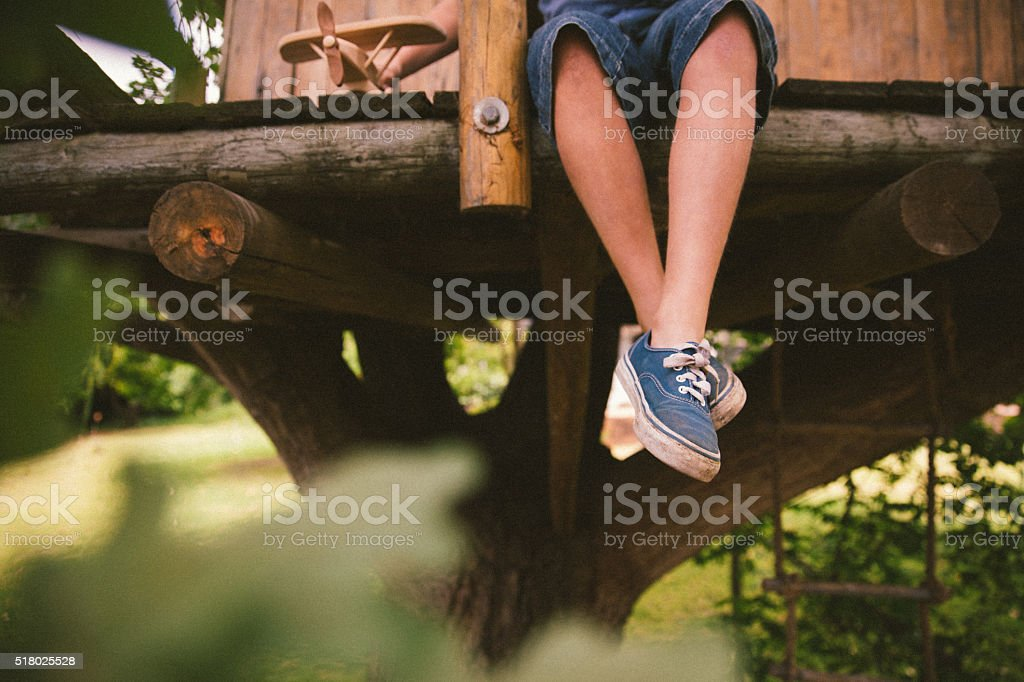 Legs of a boy over the edge of wooden treehouse stock photo