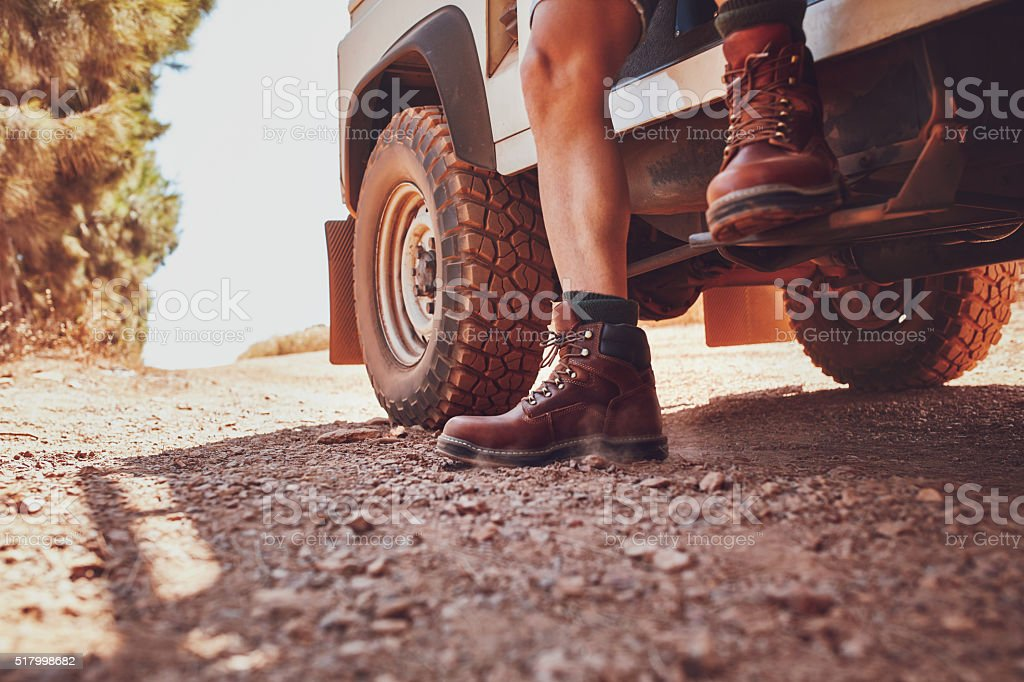 Legs of a man sitting on a off road vehicle. stock photo