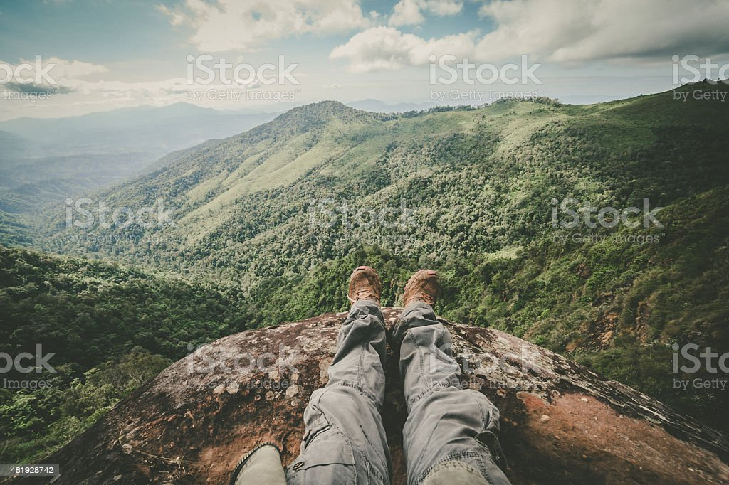Legs of a man sitting on the edge of cliff stock photo