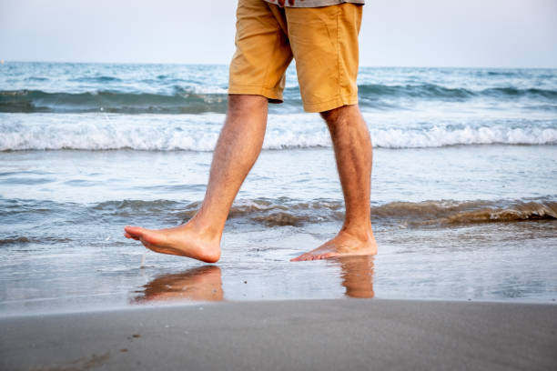 Legs of a man walking along the shore of the beach Legs of a man with short trousers walking along the shore of a mediterranean beach at sunset shorts stock pictures, royalty-free photos & images