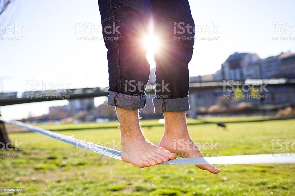 Beine von einem Mann zu Fuß auf der Slackline im Park. - Lizenzfrei Abenteuer Stock-Foto