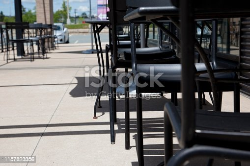 Showing the ground level view of patio tables at a restaurant outside with copy space