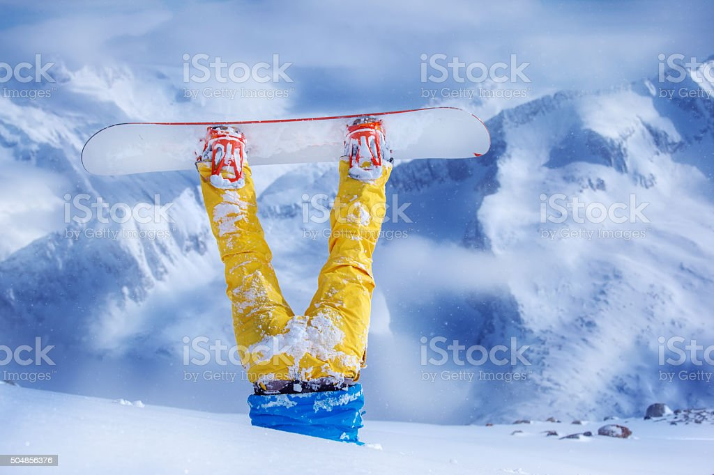 Legs of a snowboarder in yellow trousers stuck in deep snow upside...