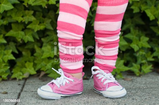 istock Legs of a toddler in pink striped leggings 139266845