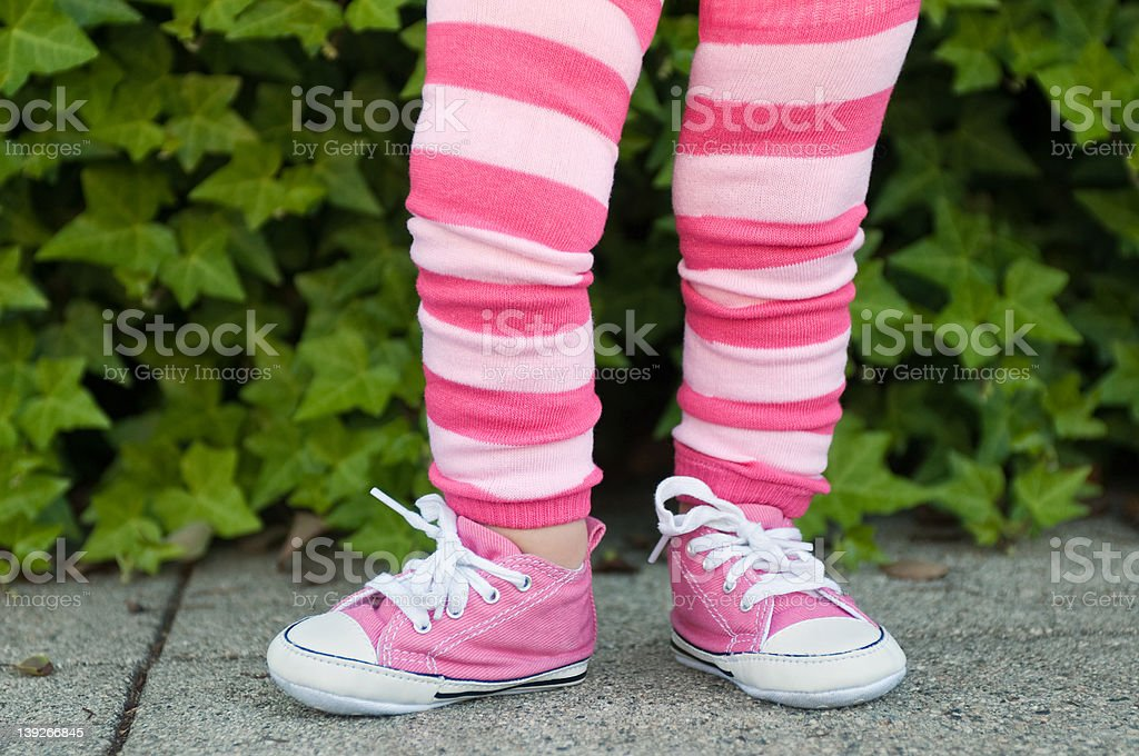 Legs of a toddler in pink striped leggings stock photo