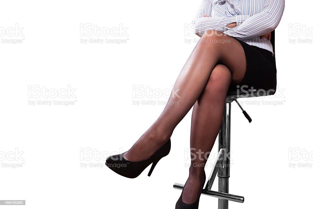 Gambe di una donna seduta su uno sgabello da bar fotografie stock