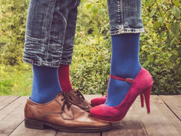 beine eines jungen paares in modischen schuhen und bunte socken - bräutigam jeans stock-fotos und bilder