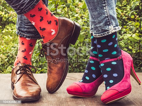 istock Legs of a young couple in stylish shoes, bright, colorful socks 1043046236