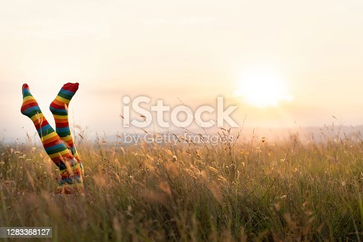 Young girl laying on the ground at sunset and has her legs in the air