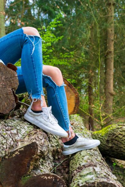 Beine einer jungen Frau, die auf gestapelten Baumstämmen sitzt. – Foto