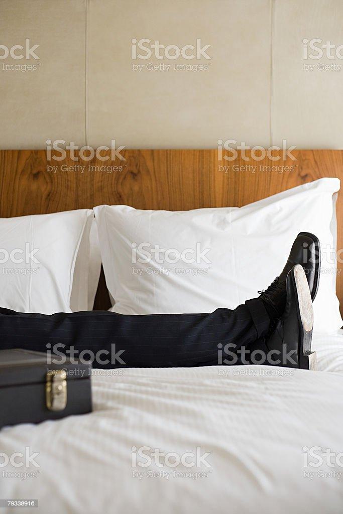 Legs of businessman on bed 免版稅 stock photo
