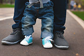 Legs of a child and an adult but asphalt. Jeans and sneakers. Paternity.
