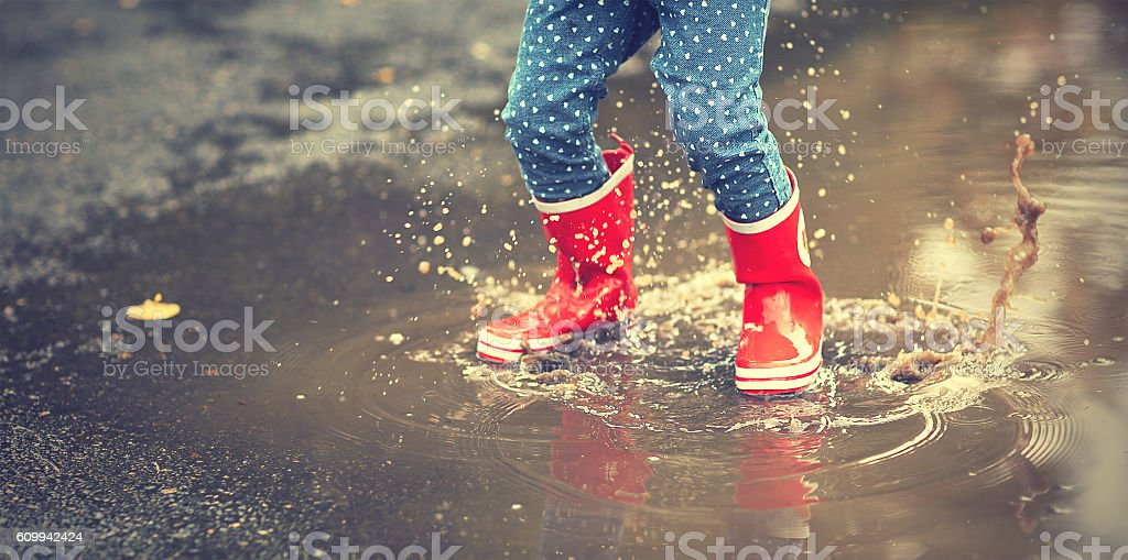 legs of child in red rubber boots jumping in puddles stock photo