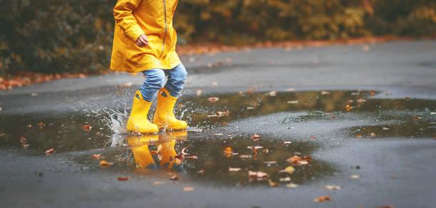 beine des kindes in gelben latex stiefel in pfütze im herbst - kinderfüße stock-fotos und bilder
